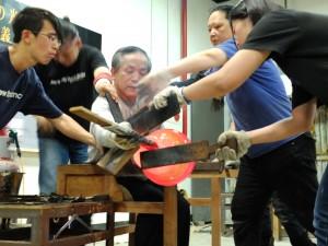 重く、高温のガラス加工には多くのスタッフを必要とし、息の合ったチームワークが要求される