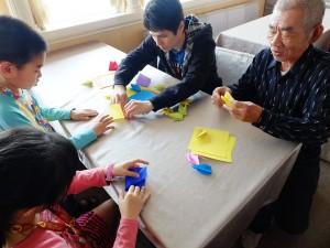 孫と一緒に折り鶴を折る男性、「昔はよく折っていたよ」と懐かしそうに話した