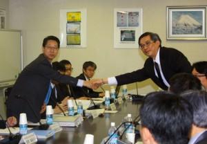 会合の成功を祈って握手する小松団長と周団長