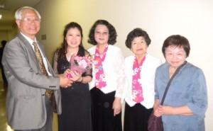 周子秋會長(左1)向吳佩娟老師(左2)及客家妹劉羅郁香團長(右2)獻花