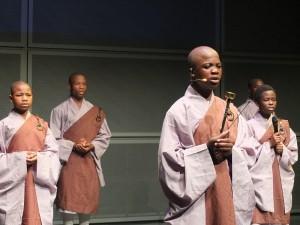 12位孩童在舞台上念誦藥師佛經