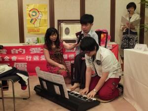 林永晏以腳彈奏電子琴和妹妹合奏