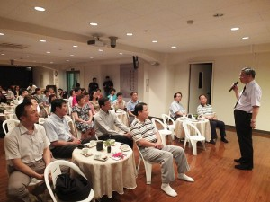 慈濟加拿大分會執行長何國慶和與會者分享參與慈濟活動的故事