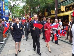 駐日代表沈斯淳伉儷(右1、2)和橫濱華僑總會會長施梨鵬(左1)走在隊伍前頭,和民眾打招呼