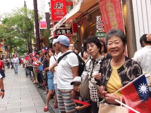 路旁的遊客也手持國旗,一同慶祝中華民國的生日