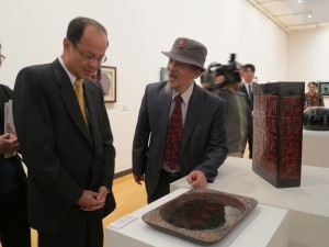 在台灣漆藝家賴作明(右)的陪同下,駐日代表沈斯淳欣賞台日漆藝家的作品