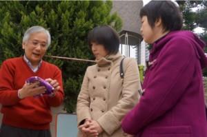 全日本崇正會聯合總會幹事長劉宏成,向日本友人解說桐花5月飄落時彷彿降雪一般的景緻