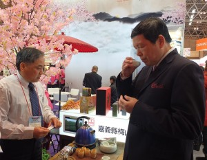 外貿協會副秘書長葉明水(右)在嘉義縣政府的攤位上試飲業者的阿里山紅茶