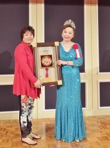 柬埔寨台灣商會副會長蔡宜晉(左)特別代表柬埔寨台商會會長贈送紀念品給謝美香