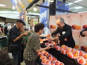 駐日副代表余吉政(右1)化身超級推銷員,加贈一顆芒果給消費者