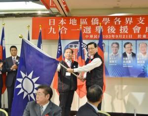 中國國民黨海外部主任夏大明(右)授黨旗給各地方分部,盼團結打贏選戰