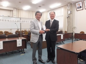 駐橫濱辦事處處長粘信士代表收下日華親善橫濱市議會議員聯盟會長森敏明(左)致贈給高雄氣爆災區的捐款