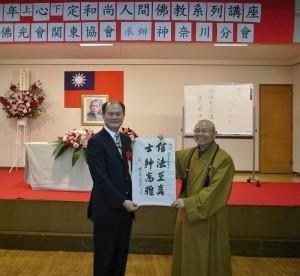 心定法師贈送駐橫濱辦事處處長粘信士(左)「信法至真,士紳高雅」的書帖一幅