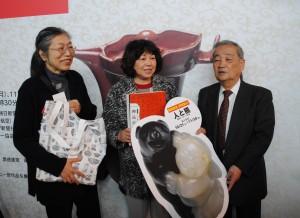 三輪館長(右)より図録を渡される福岡市の女性(中央)