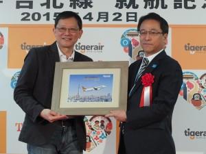 記念品の贈呈。關栩CEO(左)と成田国際空港執行役員エアライン事業部の荒川武部長(右)