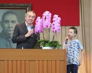 東京中華學校校長劉劍城現場直接請小學三年級的學生上台做即時翻譯