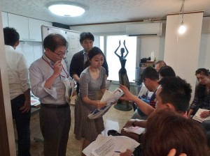 活動執行委員會的工作人員發送海報和傳單給店家發送