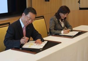 サインをするわしたみずほ銀行の林信秀頭取(左)と台湾銀行の李紀珠理事長(右)