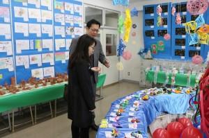 駐橫濱辦事處秘書傅國華(後)和駐日代表處僑務秘書宋惠芸特別欣賞僑校學生的創作