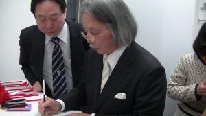 左:東京台灣商工會會長陳慶仰 陣內伯臺先生在畫冊上簽名
