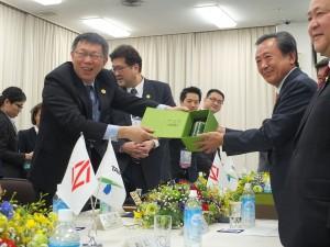 横浜市議員らに笑顔で記念品を送る柯市長