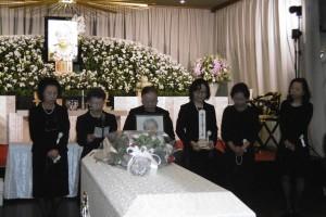 羅王阿嬤的女兒手捧靈位及遺照