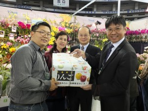 沈代表(右2)から贈られた青森のりんごを受け取る 台湾蘭花産銷発展協会の高紀清理事長(右1)と台大蘭園の頼永翔さん(左1)