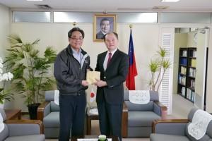 僑務委員鄭尊仁(左)熱心捐助200萬日幣,援助南台地震災區,由駐橫濱辦事處處長粘信士代表接受