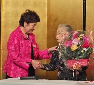 羅王明珠(右)於2015年3月8日出席婦女會慶祝活動,留日東京華僑婦女會會長吳淑娥特別致贈花束(本報資料照)