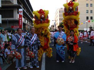 出発式で山形県日華親善協会からミニチュア花笠を受け取った鄭所長(右)