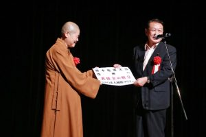 內閣府副大臣松本文明(右)收下主辦單位捐贈的熊本地震賑災款