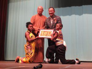子供たちからアフリカの絵をプレゼントされた元参議院議員の大江康弘氏(右上)