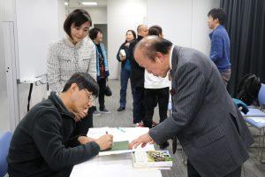 日本國際客家文化協會會長邱泱棟(右)請甘耀明簽名