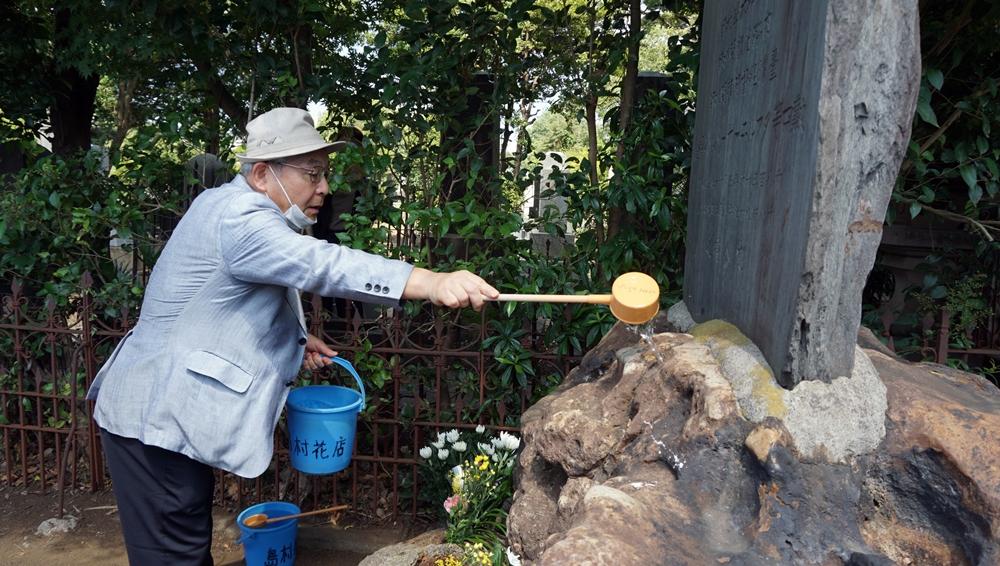 日本下水文化研究會代表稻場紀久雄替墓灑水